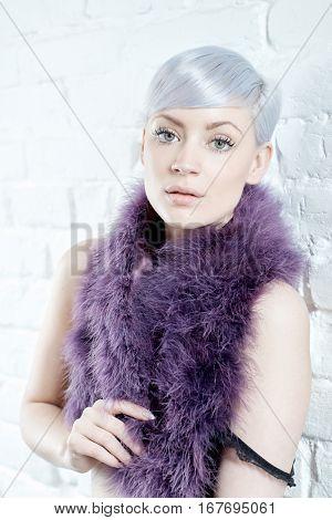 Sensual young woman in purple boa looking at camera.