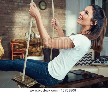 Happy young woman sitting in swing in living room, having fun. Side view.