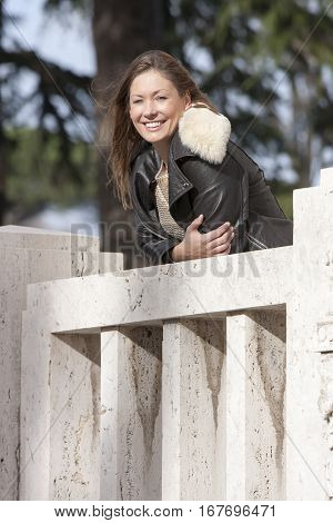 Smiling woman outdoor, overlooking on marble balcony. A beautiful girl smiling woman is resting on a marble balcony overlooking. She is dressed in a winter coat leather.