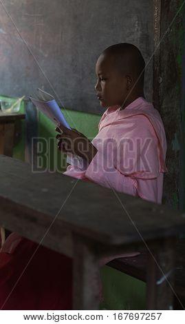 SAGAING MYANMAR - NOVEMBER 22 2016: Buddhist nun in a break between lessons read a book.