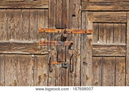 Old brown wooden door with rusty handles and locks