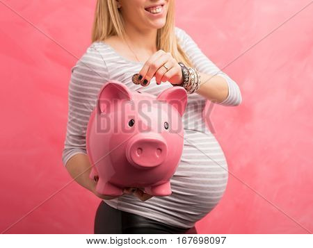 Pregnant woman saving money in piggy bank