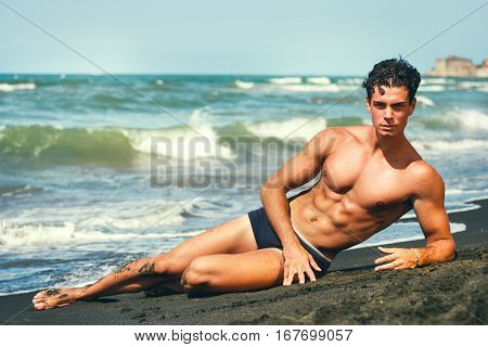 Summer. Muscular guy lying on his side. By the sea. Sculptural body. A beautiful young Italian man with a fabulous body lying on the sand by the sea. Abdominal showy.