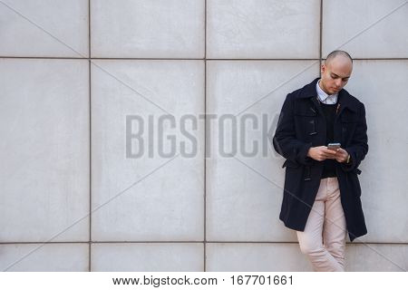Young handsome bald businessman holding a smart phone, looking down tapping screen leaning on a white wall - technology, business, work concept