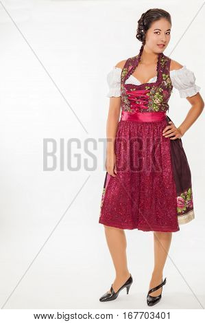 Young woman wearing a Dirndl with copy space - isolated on white.