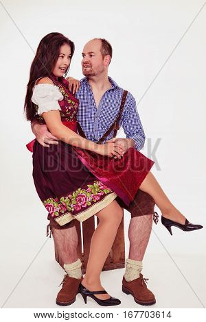 Young woman sitting in man's lap. Bavarian couple in dirndl and leather pants- isolated on white