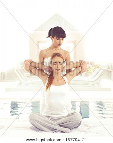 Young woman getting traditional thai stretching massage by therapist over townscape background