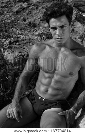 Beautiful young Italian man posing at the sea shirtless, serious and scrutinizing attitude. Athletic and muscular body, black and white.