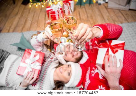 Happy couple lying on floor and toasting with champagne glasses at christmastime