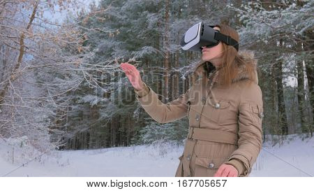 Woman putting on and using virtual reality glasses in winter forest. Virtual reality mask. VR. Future, nature, winter and technology concept
