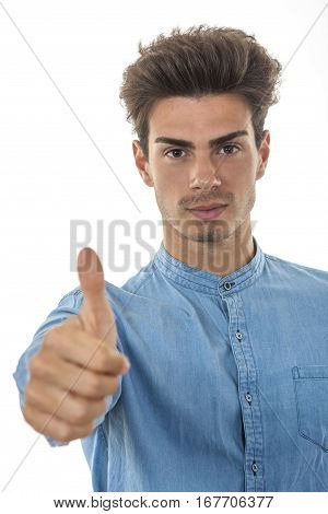 Beautiful man showing thumbs up for ok. A young man with his arm leaning forward has the thumbs up to give his consent, yeah ok sign, stylish hair.
