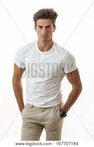 Manly male model trendy hairstyle. A young model posing in studio in trendy clothes and hairstyle, pants and shirt with six buttons, wristwatch, studio white background.