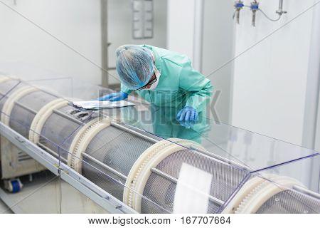 medical worker is bending on machine in pharmaciutical factory