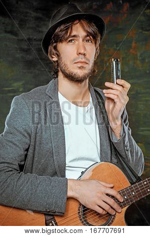 Cool guy with hat playing guitar and harmonica on gray studio background