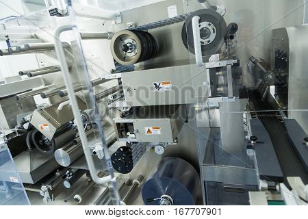 big machine with shafts and belts in pharmaciutical factory