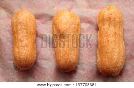 Long rows Eclair shells. Eclairs candy paper. The process of making cakes