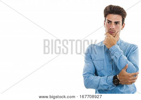 Young man model on white. Doubt and perplexity. Free empty side space. A nice boy with a blue shirt has his arms folded and his hand under his chin. Isolated on white background.