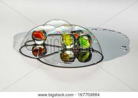 Four multi-colored glass ball inside the soap bubbles