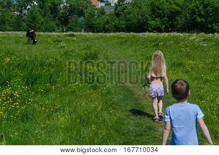 Children are walking on green grass path. A boy and a girl on a green field.