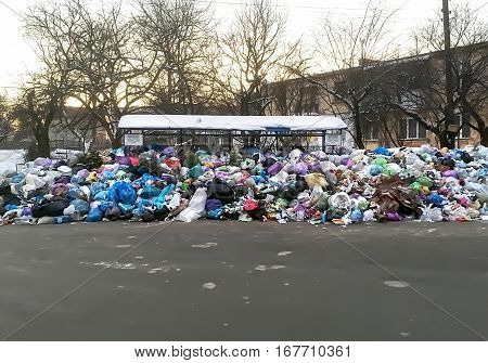 LVIV UKRAINE - JANUARY 27: Overflowing garbage cans and piles of garbage (trash) on a street in Lvov on January 27 2017 in Lviv Ukraine
