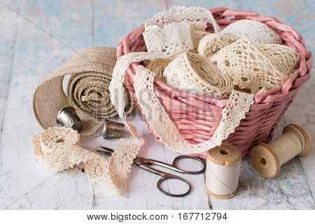 Accessories for needlework. A wicker basket with lacy ribbons, spools of thread, old scissors and thimbles on a light wooden table.
