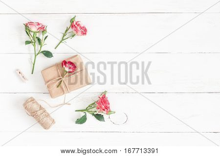 Flowers composition. Gift and rose flowers on wooden white background. Flat lay top view