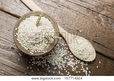 heap of white rice in wooden bowl with spoon on table.