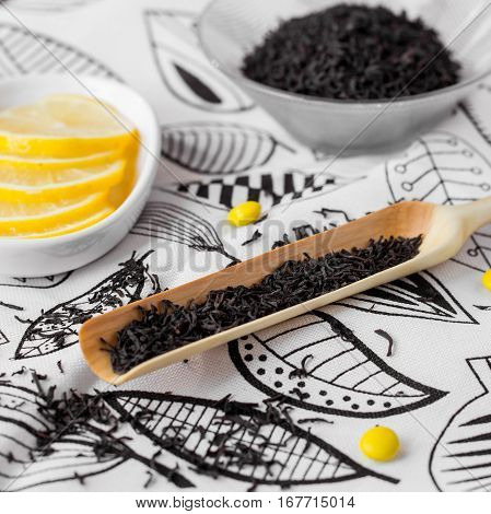 a handcarved wooden scoop full of dried black tea leaves
