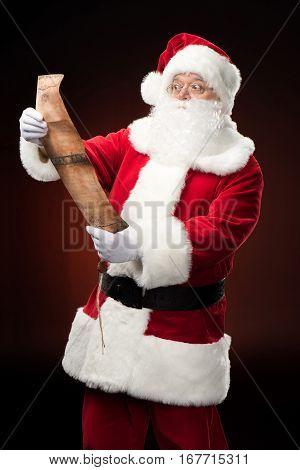 Happy Santa Claus reading wishlist against dark background