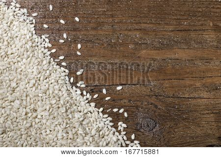 white rice scattered on wooden table with space for text.
