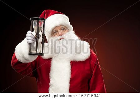 Portrait of Santa Claus showing hourglass Christmas coming