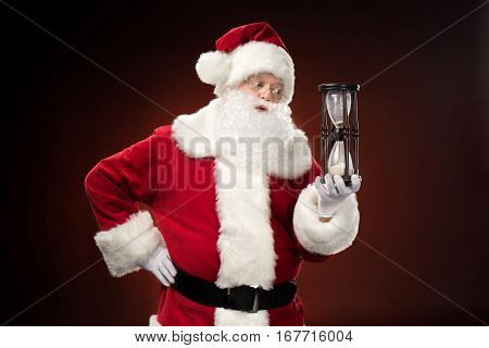 Santa Claus looking at hourglass against dark background