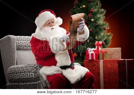 Happy Santa Claus sitting on grey armchair and reading wishlist