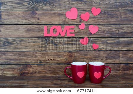 Inscription love and seven flat pink hearts on top of the two claret cup on a wooden background