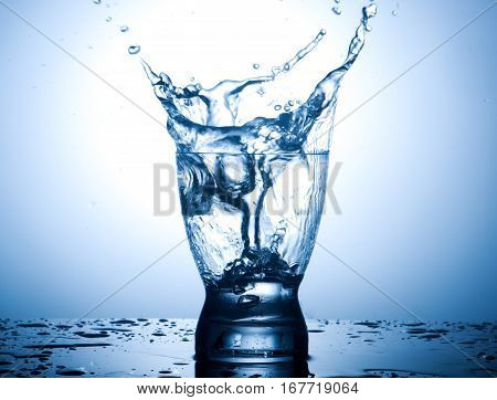 Splash in a glass of water on gradient background