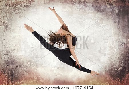 Young woman ballet dancing on wall background