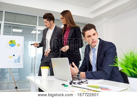 Young businessman at table on the background of his business partners.
