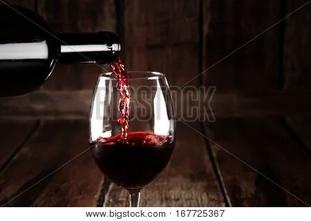 Wine in glass on brown wooden background. Red wine pour from bottle. Closeup of red wine splash. Background with red wine.