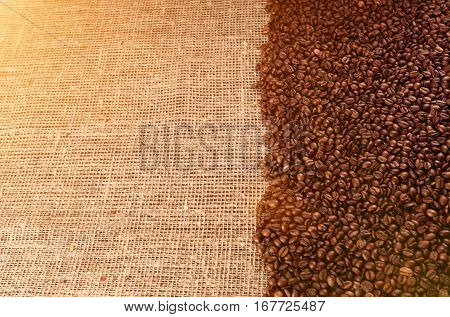 Coffee beans on sackcloth background in sunlight. Background with coffee beans and sackcloth. Free space for text on sackcloth background.