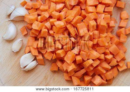 Sliced Carrots With Garlic On A Cutting Board