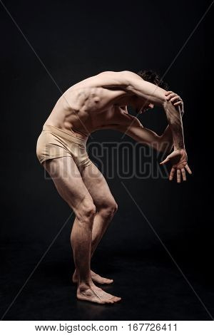 Fears inside me. Artistic flexible charismatic actor demonstrating his flexibility and expressing grace while performing in the black colored studio