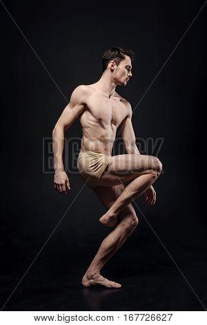 Like a manikin. Motionless concentrated skilled gymnast demonstrating his flexibility and expressing creativity while performing in the black colored studio