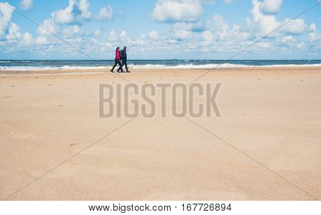 SCHEVENINGEN NETHERLANDS - AUGUST 23 2014: Cold weather in the end of the Summer in Hague; A couple walking on the north sea beach on a windy day