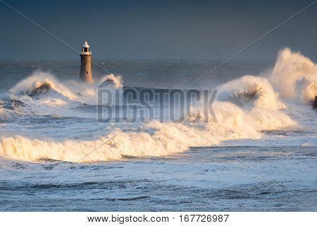 Stormy Waves at Tynemouth Lighthouse, as the sea hits Tynemouth North Pier resulting in high crashing waves cascading into the mouth of the River Tyne