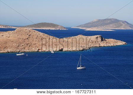 HALKI, GREECE - JULY 17, 2016: Sailing boats head into Emborio harbour on the Greek island of Halki. One hour from Rhodes, the small Dodecanese island has a population of just under 300 people.