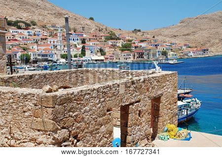 HALKI, GREECE - JULY 16, 2016: A derelict stone building stands above Emborio harbour on the Greek island of Halki. One hour from Rhodes,the Dodecanese island has a population of under 300 people.