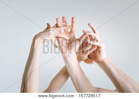 Hand plexus. Flexible sophisticated gracious athletes hands locating in the white colored studio and being tensed while expressing elegance