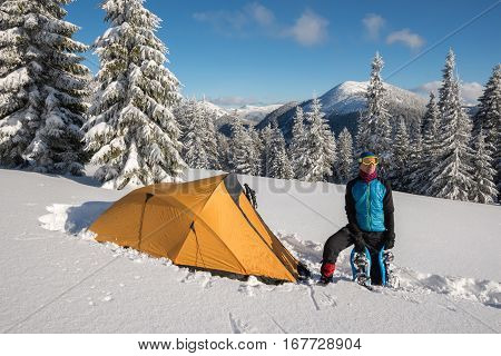 Man, Traveler With The Snowshoes Relax Near A Tent
