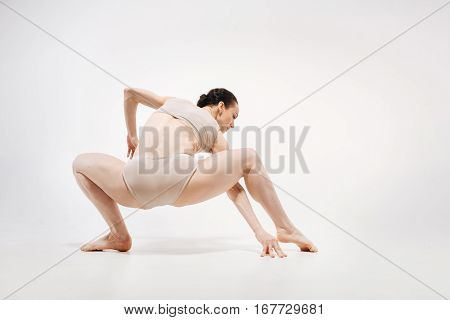 Performance of the cat woman . Graceful inspired skillful ballet dancer demonstrating her abilities and expressing elegance while dancing in the white colored room