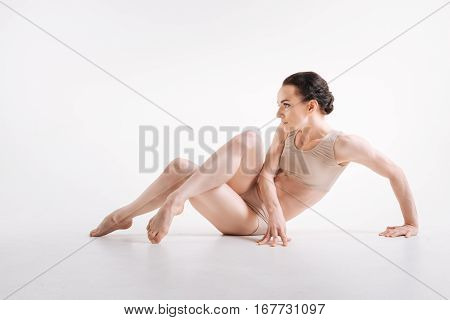 Ready to perform. Charismatic gracious sophisticated gymnast lying isolated on white floor and expressing grace while taking part in the art performance